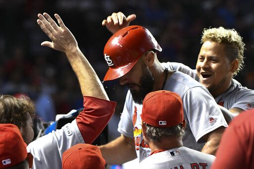 St. Louis Cardinals' Matt Carpenter, center, celebrates in the dugout with relief pitcher Carlos Martinez, right, after he hit a home run against the Chicago Cubs during the tenth inning of a baseball game Thursday, Sept. 19, 2019, in Chicago.