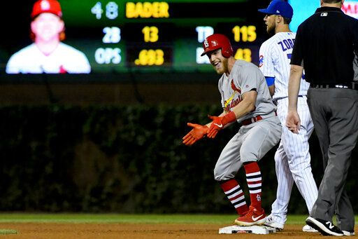 St. Louis Cardinals' Harrison Bader, third from right, reacts after hitting an RBI-double as Chicago Cubs second baseman Ben Zobrist, second from right, looks on during the sixth inning of a baseball game Thursday, Sept. 19, 2019, in Chicago.