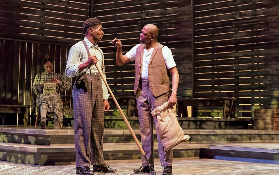"Mister (Melvin Abston), right, lectures his son, Harpo (Gilbert Domally), on how to ""control"" his wife as Celie (Eben K. Logan), left, listens in ""The Color Purple"" at Drury Lane Theatre in Oakbrook Terrace."