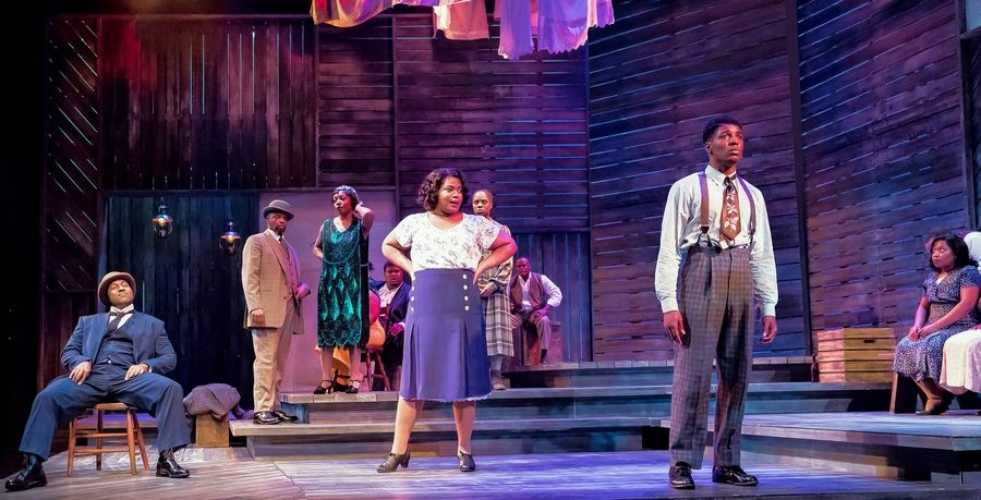 "Sofia (Nicole Michelle Haskins), center, returns to check in on her estranged husband, Harpo (Gilbert Domally), right, with her new lover, Buster (Gabriel Mudd), left and seated, in ""The Color Purple"" at Drury Lane Theatre in Oakbrook Terrace."