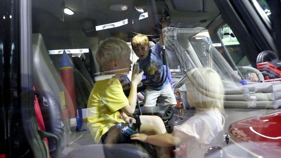 Brothers Wesley, 5, left, and JJ Wolf, 3, center, of Wheaton play with their cousin Sophia Fee, 2, of Chicago in an ambulance Saturday during Hoffman Estates' 60 anniversary celebration at the Sears Centre Arena.