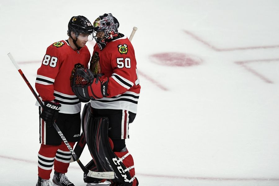 Chicago Blackhawks goalie Corey Crawford (50) celebrates with Patrick Kane (88) after the Blackhawks defeated the Detroit Red Wings in a preseason NHL hockey game Wednesday, Sept. 18, 2019, in Chicago.