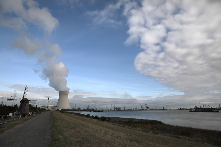 Steam rises from a nuclear power station next to an old windmill on the River Scheldt in Doel, Belgium, Thursday. Political leaders meet Monday for a climate summit in New York to ramp up global efforts to tackle the climate crisis.