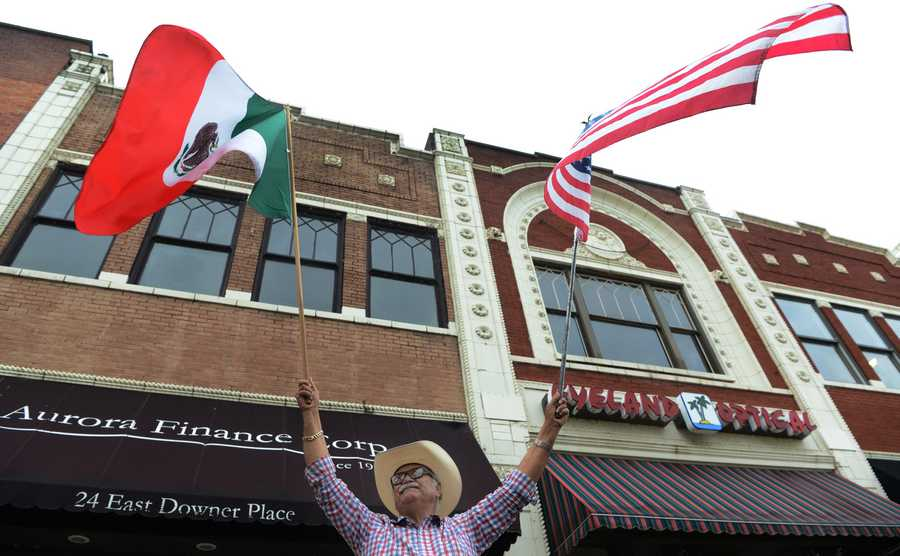 Feliciano Gutierrez, of Aurora holds both the American and Mexican flags during the Fiestas Patrias parade in Aurora on Sunday, Sept. 15.