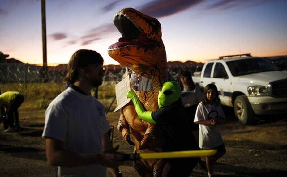 "People dressed in costumes visit an entrance to the Nevada Test and Training Range near Area 51, Friday, Sept. 20, 2019, near Rachel, Nev. People came to visit the gate inspired by the ""Storm Area 51"" internet hoax. (AP Photo/John Locher)"