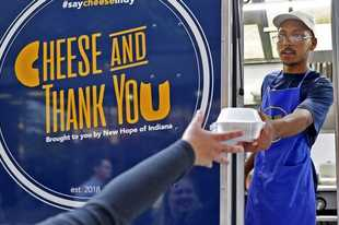 In this Friday, Sept. 6, 2019 photo, Eli Huff hands a customer her order at the New Hope of Indiana Cheese and Thank You food truck in downtown Indianapolis. The food for the food truck is prepared, served, and marketed by young adults with disabilities. Huff said he has more confidence now and plans to find another job when his food truck time comes to an end. (Kelly Wilkinson/The Indianapolis Star via AP)