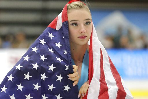 Flag-draped Amber Glenn, of the United States, skates around the rink after her third-place finish at the U.S. International Figure Skating Classic on Saturday, Sept. 21, 2019, in Salt Lake City.
