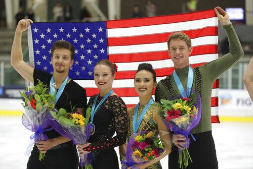 First-place finishers Madison Chock and Evan Bates, right, celebrates with Christina Carreira and Anthony Ponomarenko, left, both of the United States, following the free dance competition at the U.S. International Figure Skating Classic on Saturday, Sept. 21, 2019, in Salt Lake City.