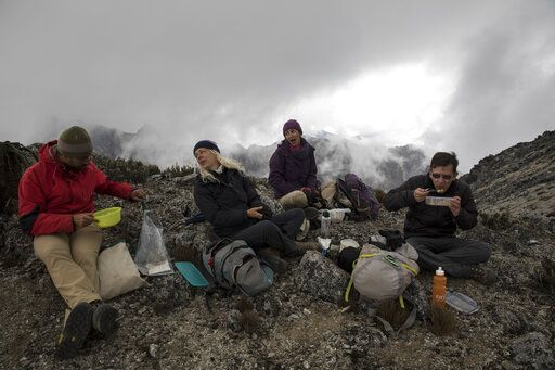 In this Feb. 19, 2019 photo, scientists have lunch during a break from a mission to study how temperatures and plant life are changing in the Andean ecosystem known as the paramos _ a mist-covered mountain grassland that lies between the top of the treeline and the bottom of the Humboldt glacier, in Merida, Venezuela. A team of scientists in Venezuela is trying to weather the political and economic crisis engulfing their country to record what happens as Venezuela's last glacier vanishes.