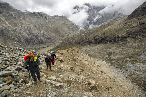 In this May 24, 2019 photo, scientists walk along a hilly path during an expedition to the Humbolt glacier, in Merida, Venezuela. While most of the planet's ice is stored in the polar regions, there also are glaciers in some mountainous regions of the tropics _ primarily in South America.