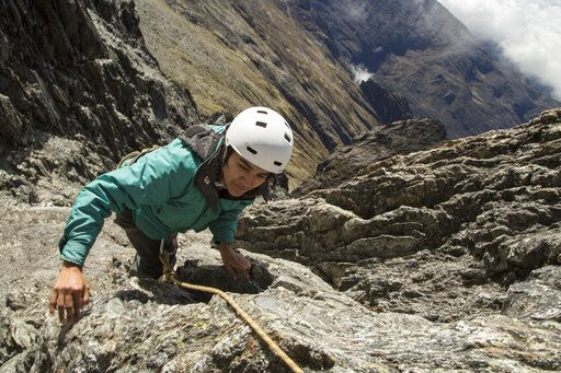 In this May 26, 2019 photo, scientist Cherry Andrea Rojas scales rocks during an expedition to the Humbolt glacier, in Merida, Venezuela. Mountain fieldwork always is physically grueling, but the deepening crisis in Venezuela since the death of former president Hugo Chavez in 2013 has transformed even simple tasks into immense hurdles.