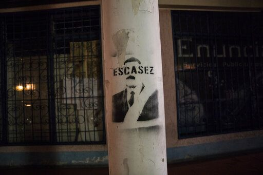 "In this Feb. 20, 2019 photo, a graffiti stencil depicts President Nicolas Maduro with the word ""Shortage,"" in Merida, Venezuela. Since the death of former president Hugo Chavez in 2013, a deepening crisis in Venezuela has transformed even simple tasks into immense hurdles."