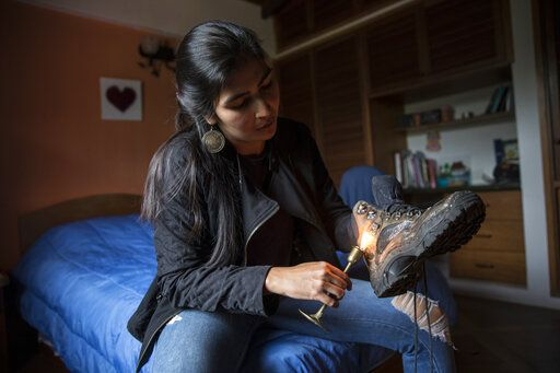 In this Feb. 18, 2019 photo, scientist Luis Mariana Cardenas uses a candle to waterproof her worn work boots in Merida, Venezuela during preparations for a mission to study how temperatures and plant life are changing in the Andean ecosystem known as the paramos _ a mist-covered mountain grassland that lies between the top of the treeline and the bottom of the Humboldt glacier.