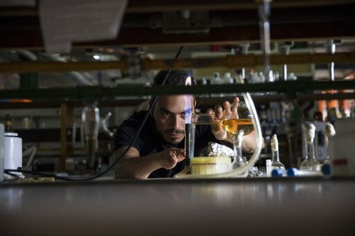 In this Feb. 20, 2019 photo, a scientist works during a blackout inside an almost empty laboratory at the Andes University, Merida, Venezuela. A team of scientists in Venezuela is trying to weather the political and economic crisis engulfing their country to record what happens as Venezuela's last glacier vanishes.