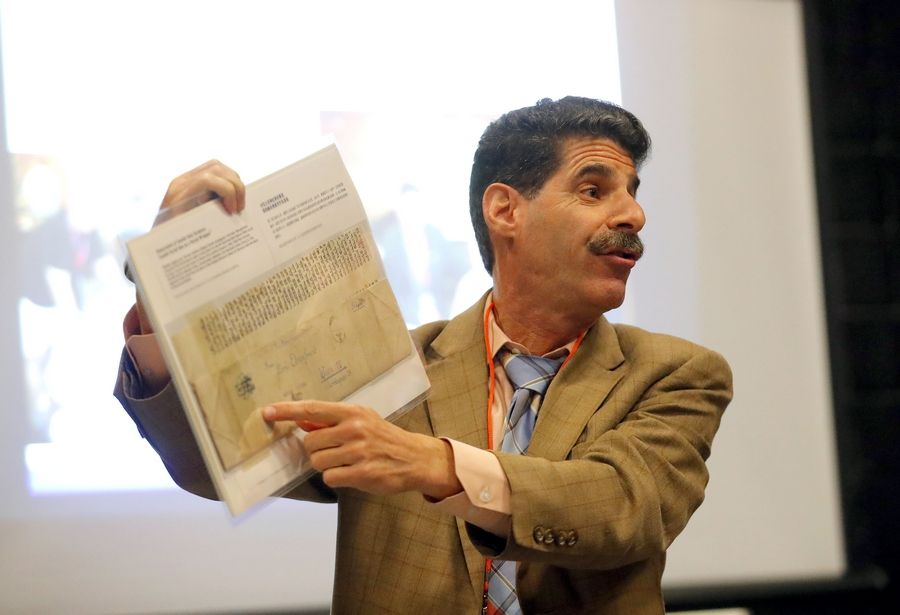 Danny Spungen of Lincolnshire displays his collection of Holocaust artifacts, including a Torah that was used to as an envelope, on Thursday at Carmel Catholic High School in Mundelein.