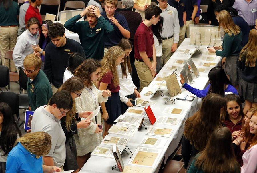 Carmel Catholic High School students examine a collection Holocaust artifacts at the Mundelein school Thursday. Carmel offers a class on the Holocaust.