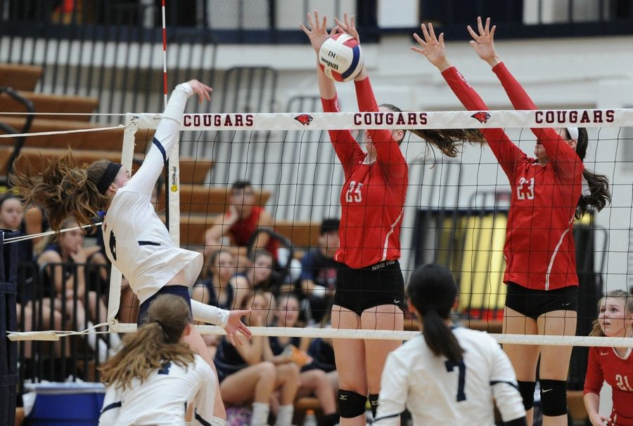 Conant's Natalie Jurgenson slams one into the arms of Palatine's Emily Campe for the block in a girls volleyball matchup at Conant on Thursday.