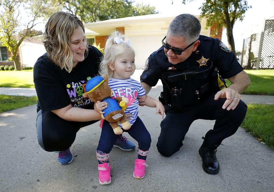 Palatine police Sgt. Art Delgadillo, right, visits with 2-year-old Alexa Mang and her physical therapist, Renee Gucciardi, as she learns to walk for the first time after facing numerous health challenges in her young life.