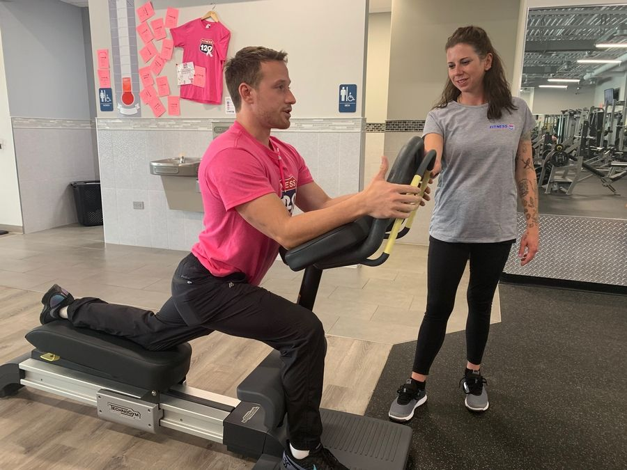 Fitness manager Ryan Mamerow demonstrates proper technique on the TechnoGym Flexability machine that measures and develops hip flexion as Fitness 120 Marketing Director Jenny DeRosa looks on. Mamerow conducts Wednesday morning high intensity interval training, open to members and non-members.