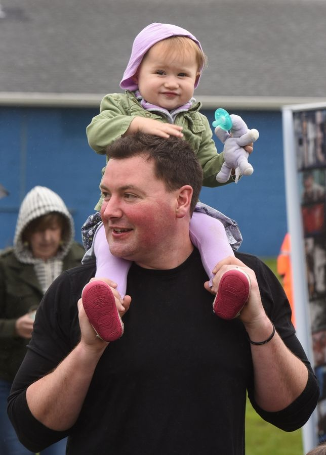 Finley Merrill, age 18 months, pats her dad Mike on top of his head as they walk through the Corks and Crafts event at the Hanover Park Sports Complex Saturday.