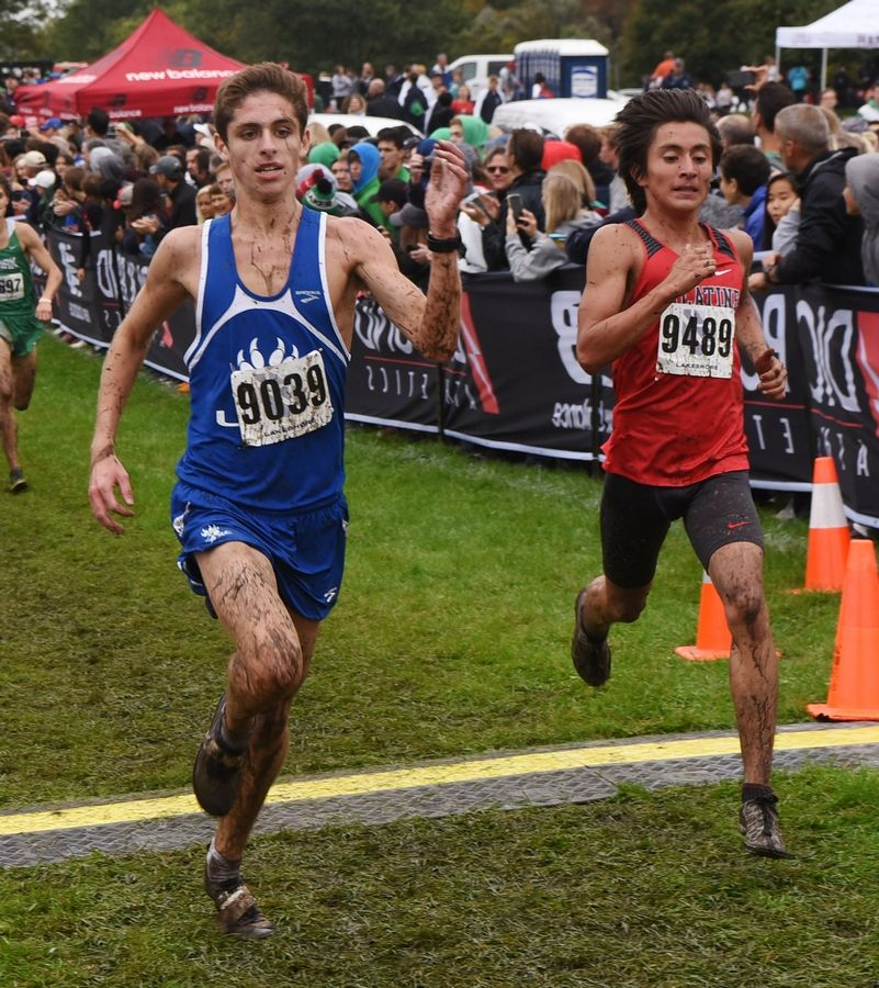 Lake Zurich's Jacob Myers, left, crosses the finish line just ahead of Palatine's Richie Jacobo during the boys varsity race of the Palatine Cross Country Invitational at Deer Grove East Forest Preserve in Palatine Saturday.