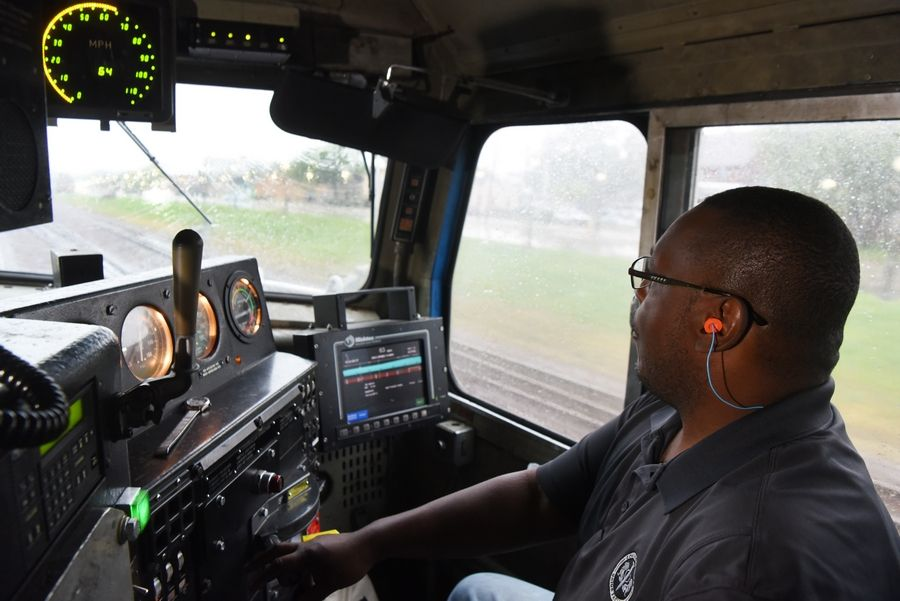 Union Pacific engineer Gregory Grayer is at the throttle of a Metra train rolling westbound at 64 mph on the Union Pacific West Line. He shared his cab as part of a train safety event Friday.