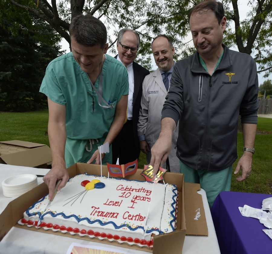 Dr. Scott Otto and Dr. Scott Miller cut the anniversary cake as Advocate Condell Medical Center President Mike Ploszek and Dr. William Watson look on during the Tuesday's 10th anniversary celebration of Condell's Level 1 trauma center in Libertyville.