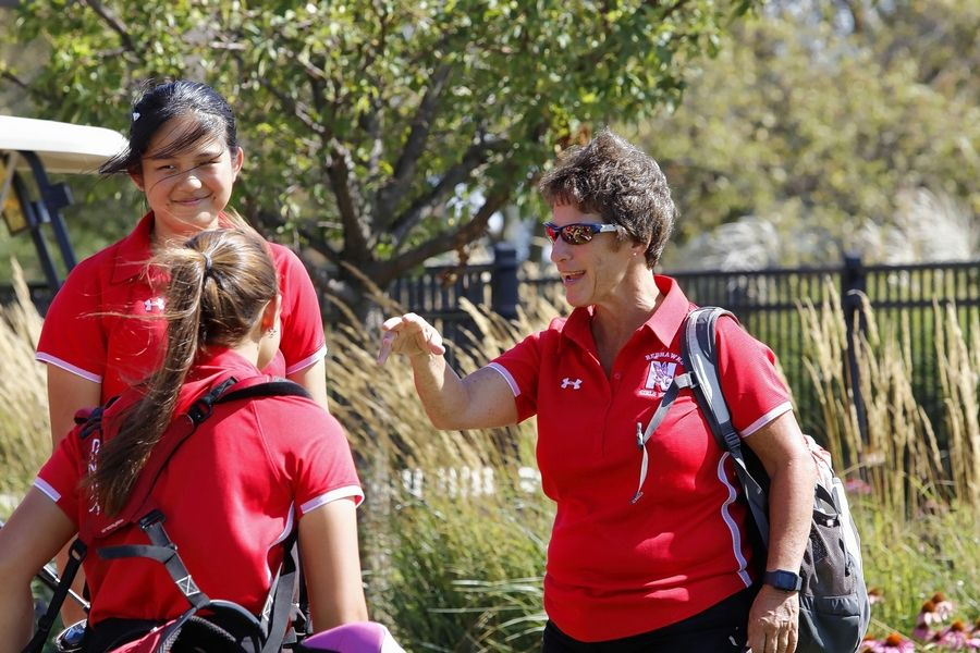 Naperville Central girls golf coach Jane Thompson shares a moment with Redhawks golfers Becki Zhang (rear) and Ava Lyons.