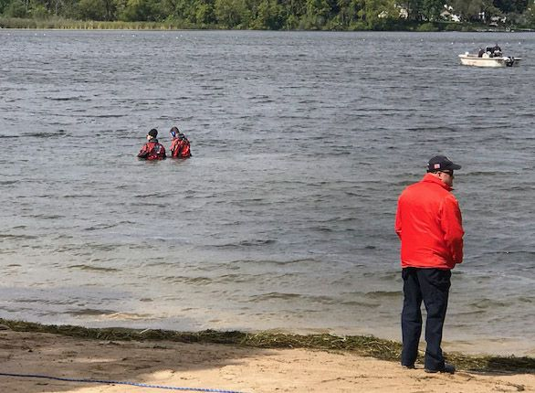 Divers and investigators searched in Round Lake and on the adjoining beach across for the Round Lake Park village hall Thursday for potential evidence involving a shooting early Sunday at a home on the 500 block of Fairlawn Drive in which one man was killed and three others injured.