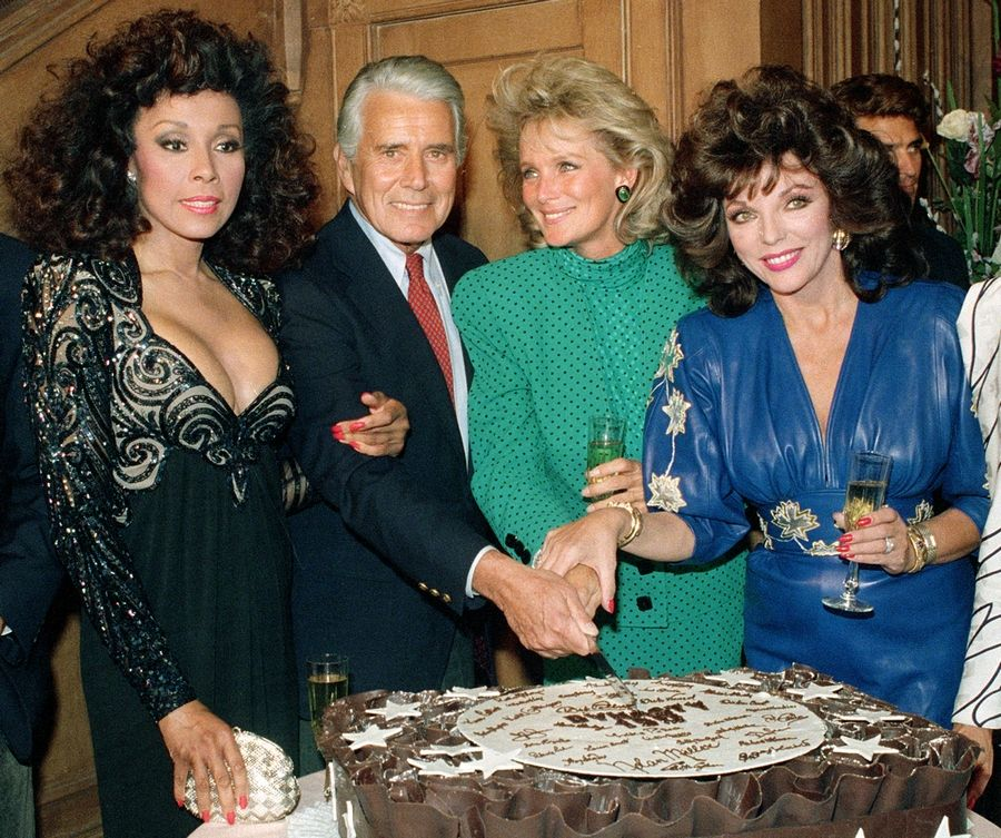 "FILE -- This Sept. 24, 1986 file photo shows, Diahann Carroll, John Forsythe, Linda Evans and Joan Collins from ""Dynasty"" cutting a cake to commemorate the production of 150 episodes of the show in Los Angeles. Carroll died, Friday, Oct. 4, 2019, at her home in Los Angeles after a long bout with cancer. She was 84."