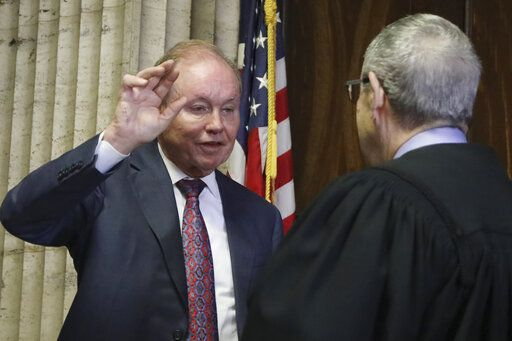 In this Aug. 23, 2019 photo, former U.S. Attorney Dan Webb takes the oath of special prosecutor before Judge Michael Toomin, during an status hearing concerning actor Jussie Smollett at the Leighton Criminal Court building, in Chicago. The latest twist in the Jussie Smollett saga is the revelation of a possible conflict of interest by the special prosecutor investigating why prosecutors dropped charges accusing the actor of staging a racist, homophobic attack on himself. Dan Webb disclosed this week he once co-hosted a political fundraiser for a figure central to his investigation, Cook County State's Attorney Kim Foxx. A Cook County judge must now decide if bias or the appearance of bias renders Webb's position untenable.(Antonio Perez/ Chicago Tribune via AP, Pool)