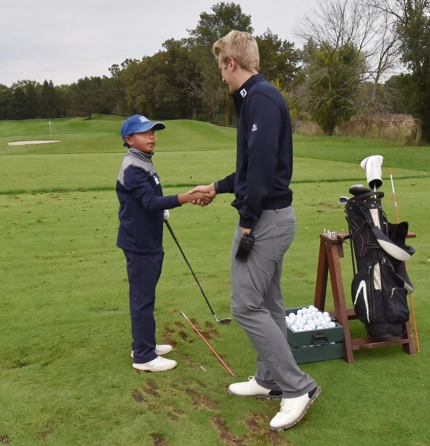 Carson Valeroso, 11, of Long Grove shakes hands with Ivanhoe Club intern Quinn Tank on the practice green as kids in the First Tee program learn golf skills in Mundelein Saturday. The program also teaches young golfers life skills.