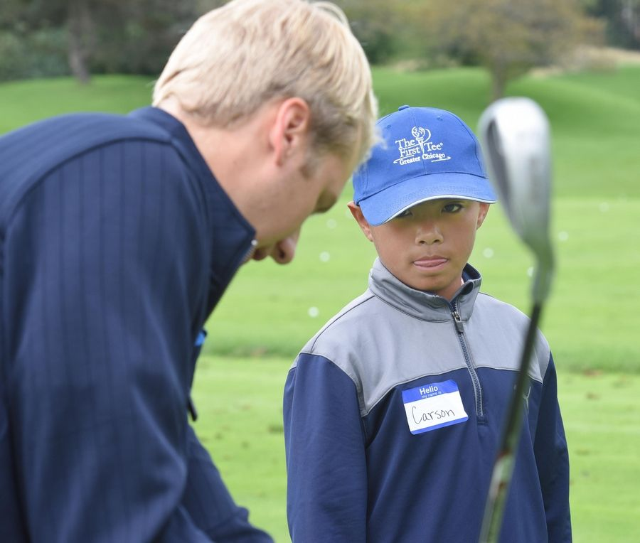 Carson Valeroso, 11, listens to Ivanhoe Club intern Quinn Tank on the practice green as kids in the First Tee program learn golf skills in Mundelein Saturday.