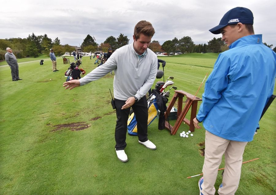 Zack Ross, an intern at Ivanhoe Club in Mundelein, talks about weight distribution on the practice tee as kids in the First Tee program learn golf skills Saturday.