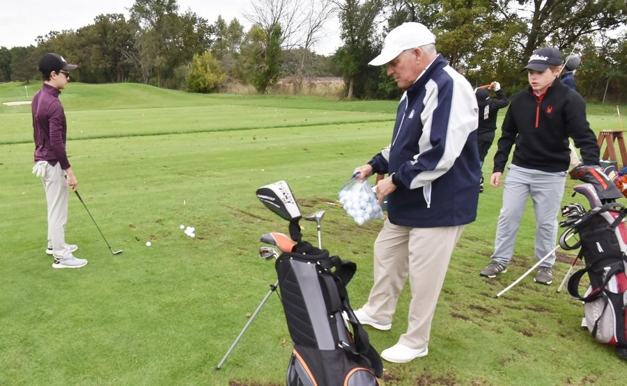 Jim Brownlie of the Ivanhoe Club gives participant golf balls on the practice tee as almost 20 kids in the First Tee program learn golf skills in Mundelein Saturday.