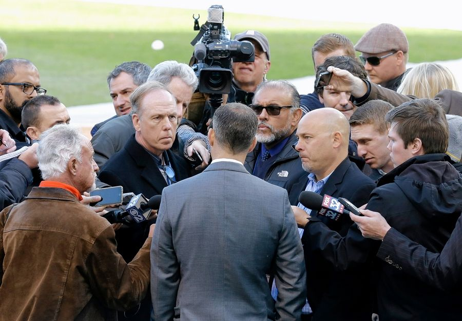 Cubs president Theo Epstein, facing away, talks to media at Wrigley Field before the start of an opening day baseball game against the Cincinnati Reds on April 11, 2016, in Chicago. Daily Herald beat writer was to Epstein's left.