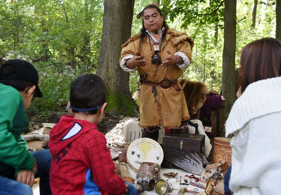 Redhawk, who said he was representing the native people of the Great Lakes area, shows off some historical memorabilia Sunday during the Schaumburg Autumn Harvest Festival at the Spring Valley Nature Center.