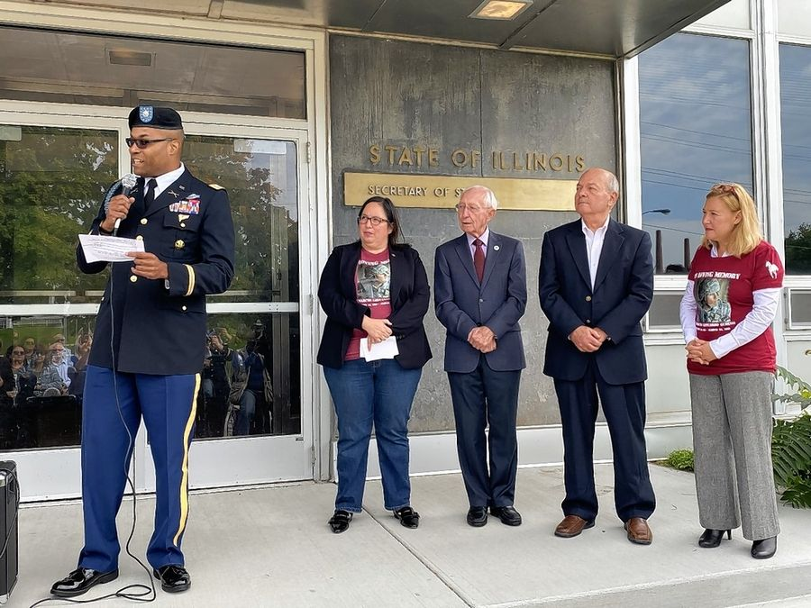 Lt. Col. Milton R. Ware of the Illinois Army National Guard speaks Sunday during a ceremony renaming a bridge in Elgin after Sgt. Marcos Gudino, who was killed in a crash last year while driving home from training exercises. Looking on, left to right, are state Sen. Cristina Castro, Elgin Community College Trustee John Duffy, Elgin Mayor David Kaptain, and state Rep. Anna Moeller.