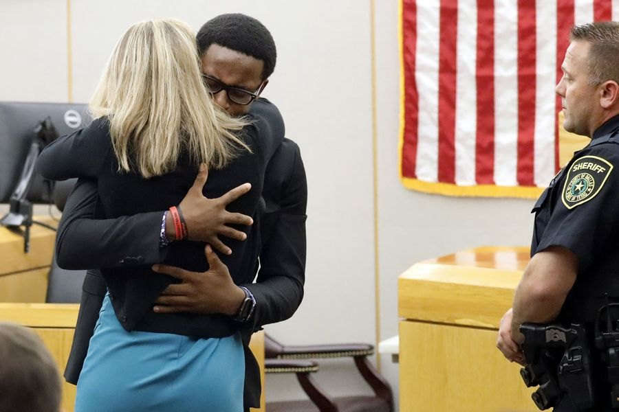 Brandt Jean hugs convicted murderer and former Dallas police officer Amber Guyger after delivering his impact statement. Guyger was sentenced to 10 years for killing Jean's brother Botham.