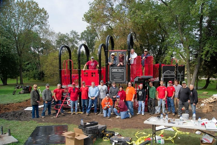 Volunteers pose with the finished product after helping to install a piece of railroad-themed piece of playground equipment over the weekend, the first upgrade in about 20 years at what is commonly known as Caboose Park in Lake Villa Township.