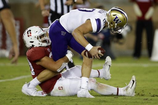 Washington quarterback Jacob Eason is sacked by Stanford's Scooter Harrington, left, in the second half of an NCAA college football game Saturday, Oct. 5, 2019, in Stanford, Calif.