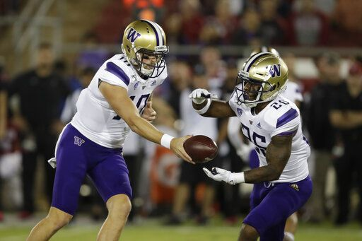 Washington quarterback Jacob Eason, left, hands the ball off to Salvon Ahmed (26) during the first half of an NCAA college football game against Saturday, Oct. 5, 2019, in Stanford, Calif.