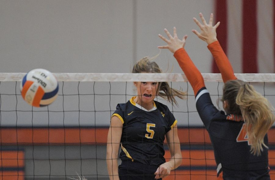 Neuqua Valley's Riley Ammenhauser gets a shot past Naperville North's Ellie Hall in a girls volleyball game in Naperville Tuesday.