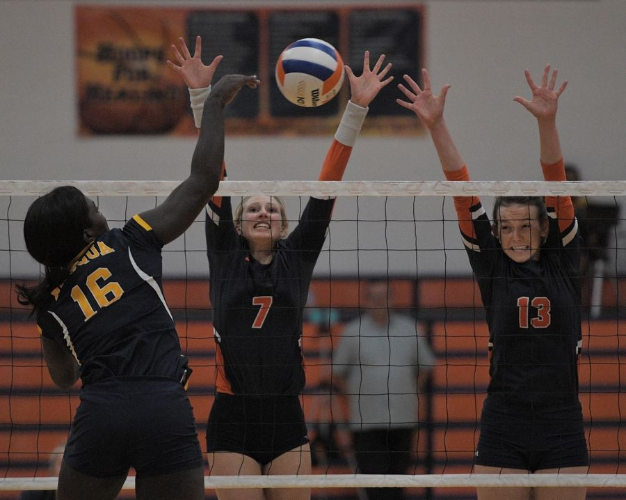 Neuqua Valley's Faith Johnson sends a shot into the defense of Naperville North's Rachel Rahtz and Kara Oxenknecht in a girls volleyball game in Naperville Tuesday.