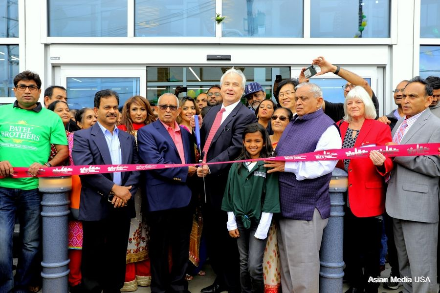Niles mayor Andrew Przybylo cuts the ribbon with store co-founders Mafat Patel, left, and store founders Tulsi Patel, right, during the grand opening of Patel Brothers on October 3, 2019 Thursday in Niles Suresh Bodiwala