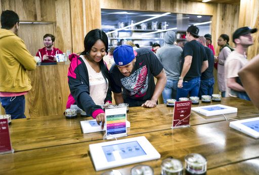 FILE - In this May 19, 2018 photo tourists Randy Wilkie and Keya Cole from Buffalo, New York, check out the offerings of cannabis at one of the MedMen cannabis dispensaries in Los Angeles. Marijuana stocks have come down hard from their highs a year ago, and the skid isn't just spooking investors. On Tuesday, Oct. 8, 2019, MedMen Enterprises Inc., which sells legal cannabis in California and 11 other states, backed out of a blockbuster deal to buy PharmaCann, a Chicago-based marijuana company with operations in eight states.