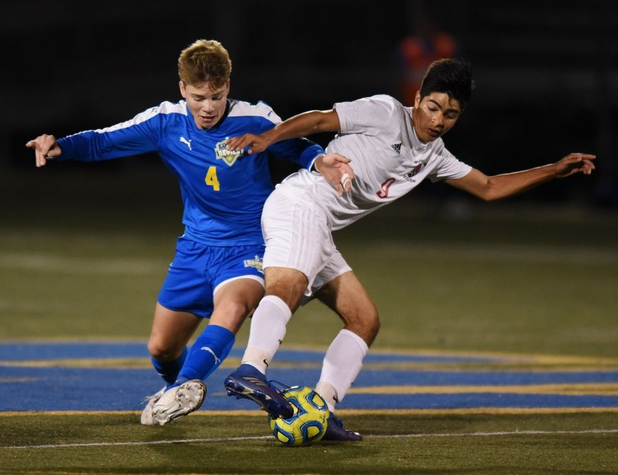 Warren's Max Floriani, left, and Mundelein's Jesus Abrego battle for position during Tuesday's match in Gurnee.