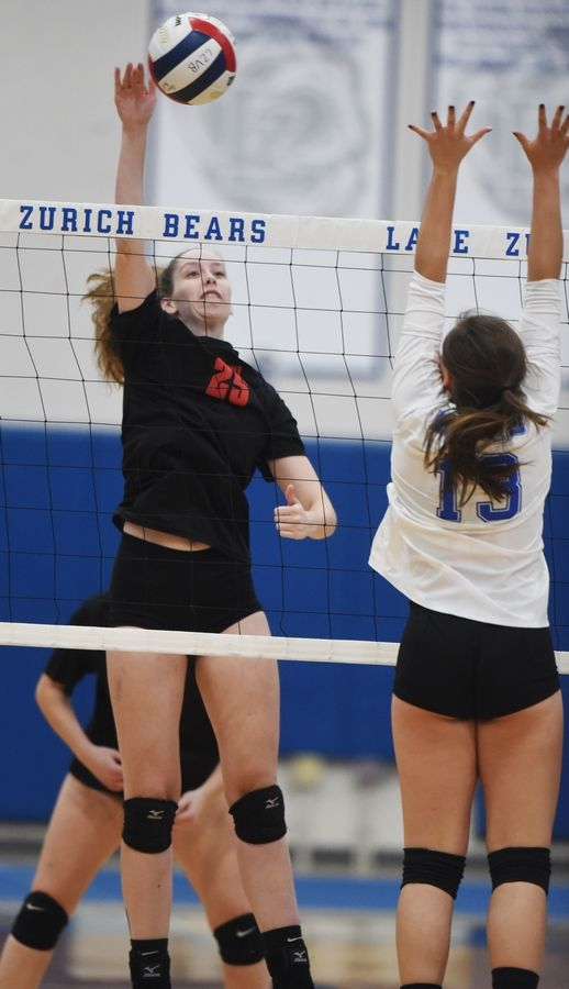 Palatine's Emily Campe leaps for a kill in front of Lake Zurich's Jarynn Hartman Wednesday.