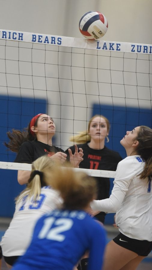 The ball is balanced on top of the net for a moment as Palatine's Sarah Elischer, left, and Lake Zurich's Maddie Gillis wait for it to come down Wednesday.