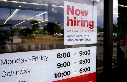 "FILE - In this Aug. 15, 2019, file photo a ""Now hiring"" sign is displayed on the front door of a Staples store in Manchester, N.H. On Wednesday, Oct. 9, the Labor Department reports on job openings and labor turnover for August."